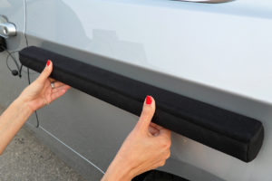 A woman applying the Doordefender Original car door protector